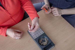 Die Patientin beim Fertigkeitstraining für die Finger ihrer linken Hand